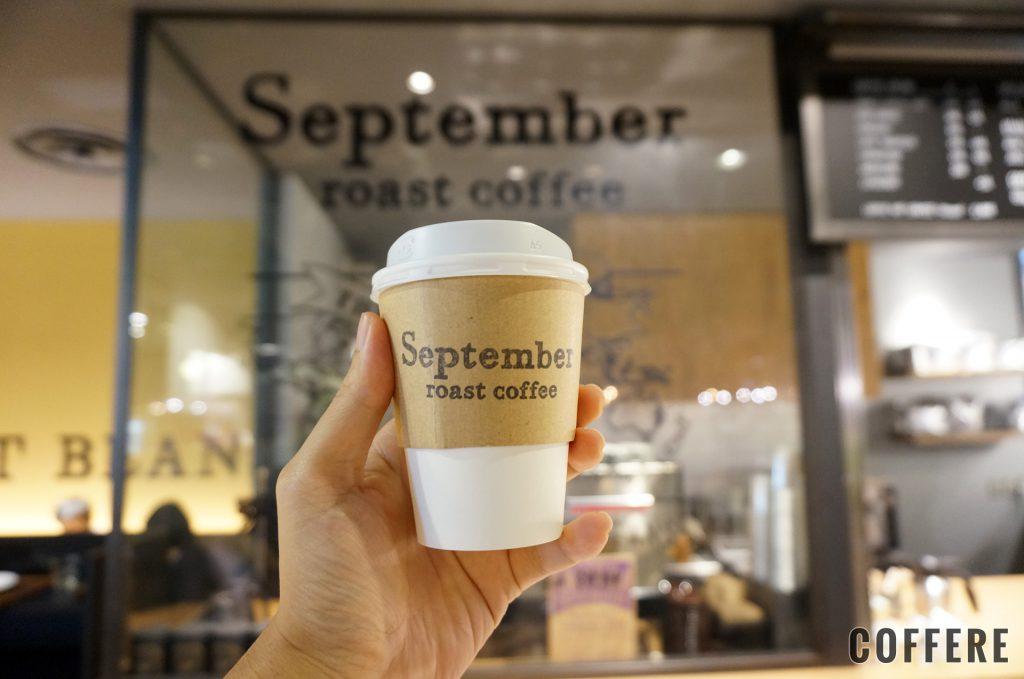 September roast coffeeのテイクアウトカップ。ロゴの前で