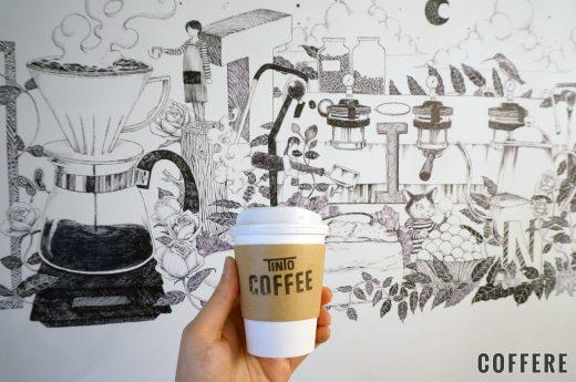 TINTO COFFEEのテイクアウトカップと壁の絵