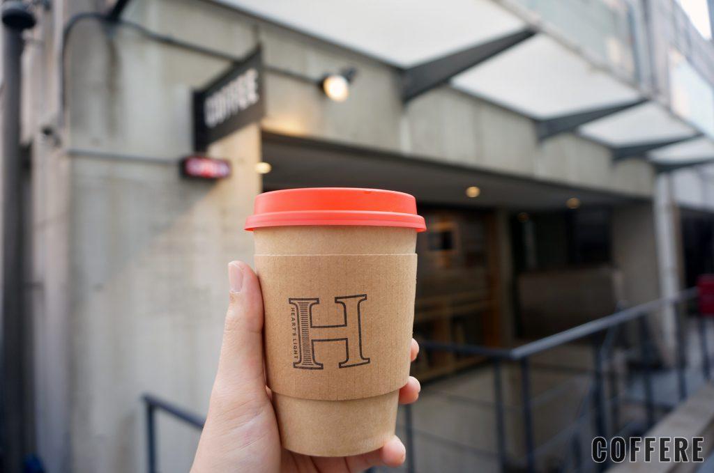hand with HEART'S LIGHT COFFEE coffeecup
